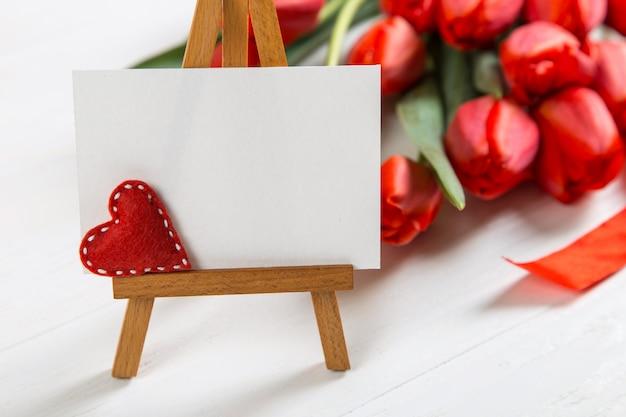 Ein zeichen gegen eine der roten tulpen auf weißem tisch. das konzept des muttertags. speicherplatz kopieren.