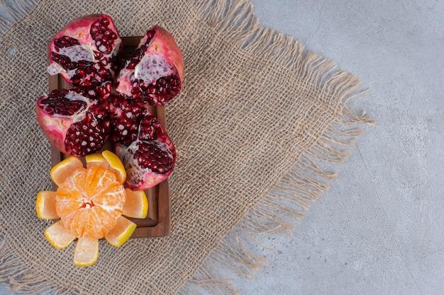 Ein zerbrochener granatapfel und eine geschälte mandarine auf einem stück stoff auf marmorhintergrund.