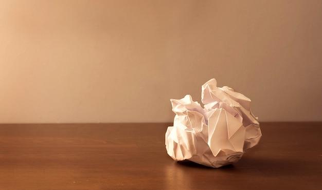 Ein zerknittertes blatt papier liegt auf einem holztisch.