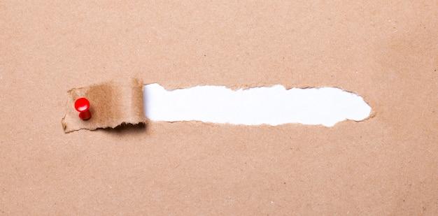 Ein zerrissener streifen bastelpapier wird mit einem roten knopf festgesteckt. im inneren befindet sich weißes papier