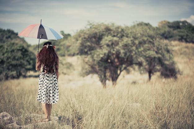 Ein zigeunermädchen, das regenschirm und stand alleine in der wiese hält