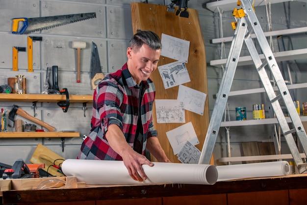 Ein zimmermann arbeitet. zimmermann studiert zeichenprojekt. vor dem hintergrund des workshops.