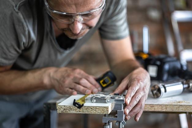 Ein zimmermann dabei, ein professionelles werkzeug zum präzisionsbohren in holz.