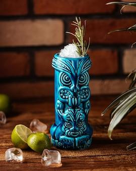 Ein zitronencocktail von vorne mit zitronenscheiben und eiswürfeln im souvenirglas auf dem tisch trinkt saftcocktail