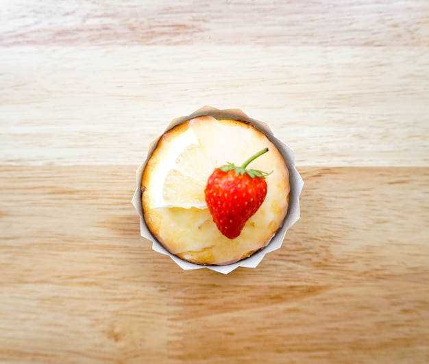 Ein zitronenkuchen mit einem stück erdbeere auf einem holztisch