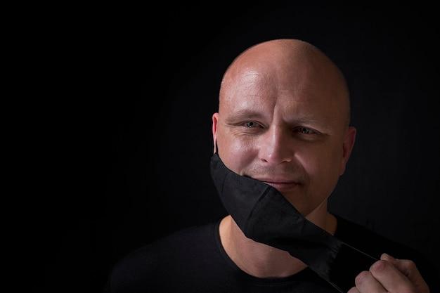 Ein zufriedener glatzkopf mittleren alters nimmt seine schwarze medizinische maske ab. schwarzer hintergrund