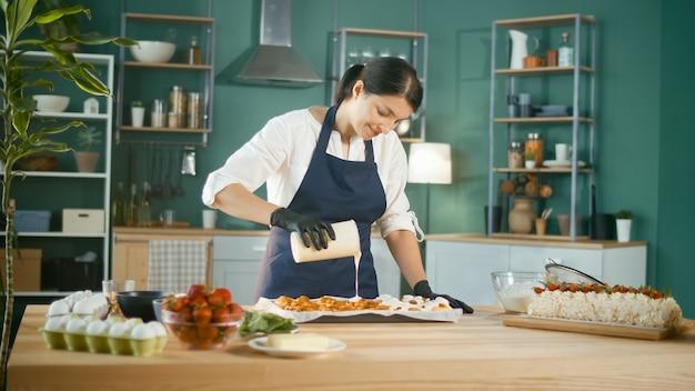 Ein zufriedener konditor gießt sahnehäubchen auf frisch gebackene zimtschnecken oder zimtschnecken