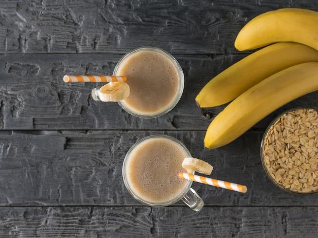 Ein zweig bananen, smoothies und haferflocken auf einem holztisch