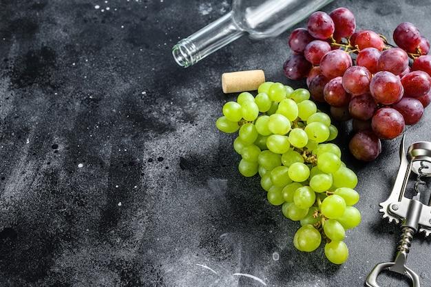 Ein zweig grüner und roter trauben, eine flasche, ein korkenzieher und ein korken. konzept der weinherstellung. schwarzer hintergrund