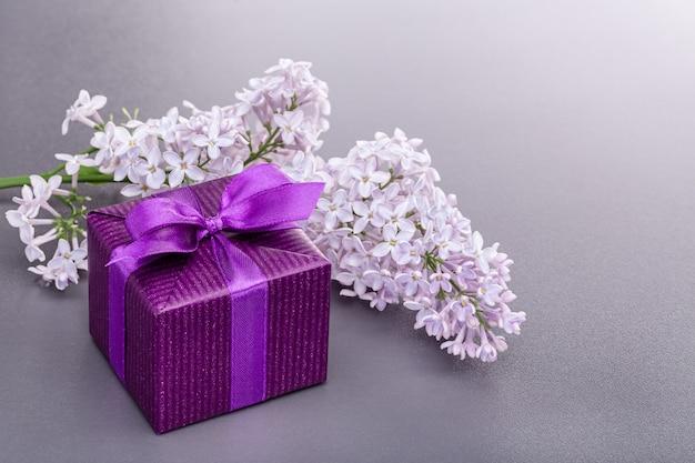 Ein zweig lila blumen, überraschung in lila geschenkbox.