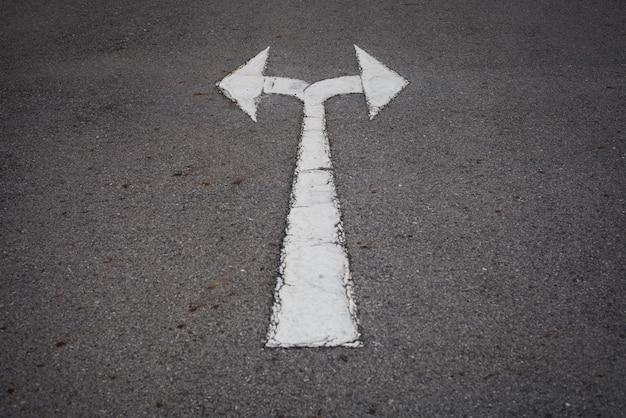 Ein zweiwegpfeilsymbol auf einer schwarzen asphaltstraßeoberfläche.