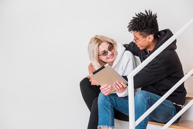 Ein zwischen verschiedenen rassen junges paar, das auf treppenhaus unter verwendung der digitalen tablette gegen weiße wand sitzt