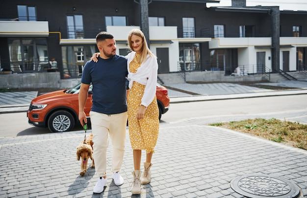 Einander umarmen. schönes paar geht zusammen mit hund draußen in der nähe des autos spazieren.