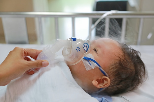 Einatmungsbabyalter ungefähr 1 jahre alt auf geduldigem bett. respiratory syncytial virus (rsv)