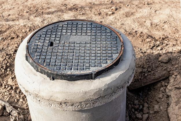 Einbau einer straßenmetallluke in einen betonbrunnen. nahaufnahme. straßenarbeiten. schutz von unterirdischen versorgungsleitungen und brunnen.