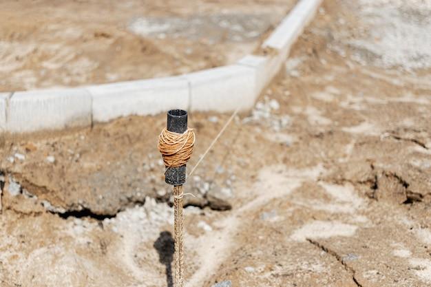 Einbau eines betonbordsteins auf einem seilsteg. werkzeug für bau- und straßenarbeiten. unscharfer hintergrund.