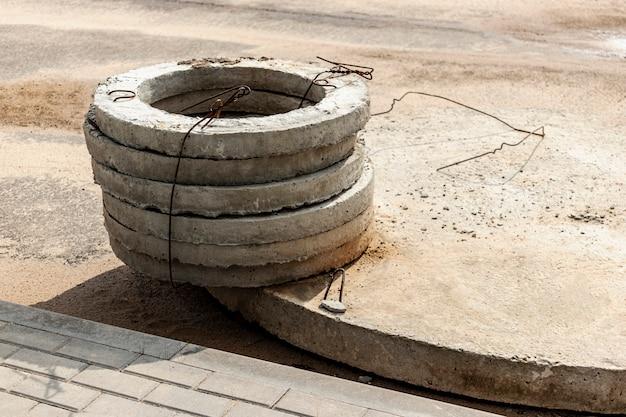 Einbau von betonkanalbrunnen in den boden auf der baustelle. die verwendung von stahlbetonringen für senkgruben, überlauf-klärgruben. verbesserung von brunnen und regenwasser.