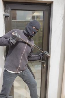 Einbrecher, der in haus unter verwendung der krähenstange einbricht