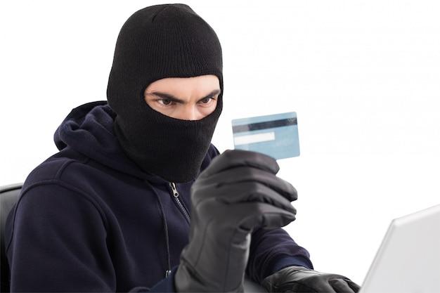 Einbrecher, der kreditkarte und laptop verwendet