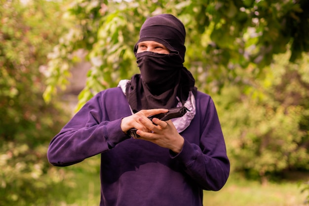 Einbrecher in maske hält und lädt die pistole im freien