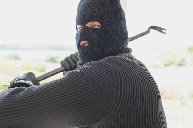 Einbrecher mit brechstange in seiner hand
