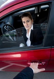 Einbrecher versucht, in das auto einzubrechen. verängstigte frau, die die tür blockiert