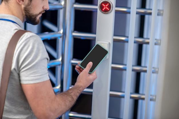 Eindringschutz. bärtiger junger mann, der smartphone anwendet, um auf scanner am drehkreuz der eingangsorganisation zuzugreifen