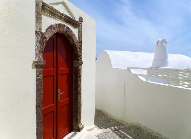 Eindrucksvolles griechisches art-tür-gehäuse mit roter tür auf weißem gebäude bei santorini, griechenland
