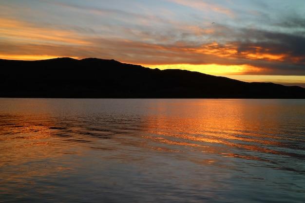 Eindrucksvolles sonnenuntergang-nachglühen, das über den berühmten titicaca-see in puno, peru nachdenkt