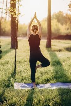 Eine 36-jährige frau praktiziert yoga an einem frühen sonnigen morgen im wald zwischen den bäumen. weicher selektiver fokus.