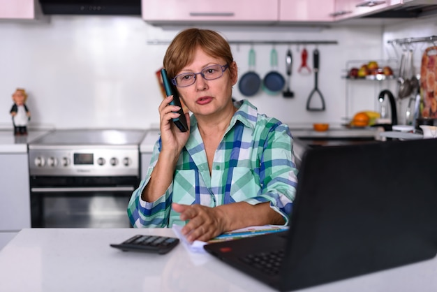 Eine 65-jährige frau arbeitet zu hause online per laptop und telefoniert