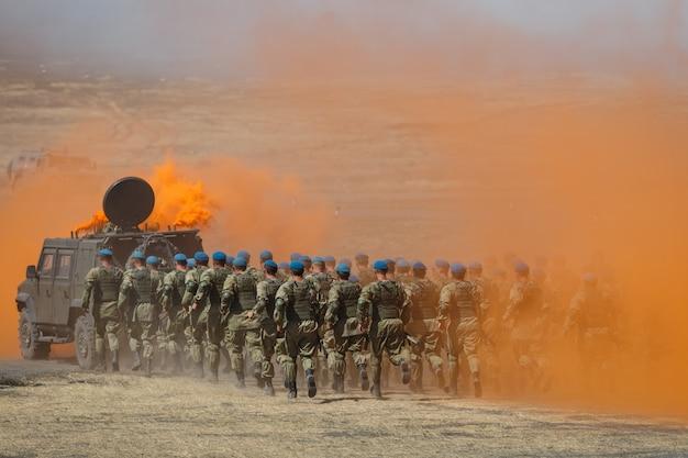 Eine abteilung russischer fallschirmjäger rennt in schützendem orangenrauch für ein gepanzertes auto über das feld