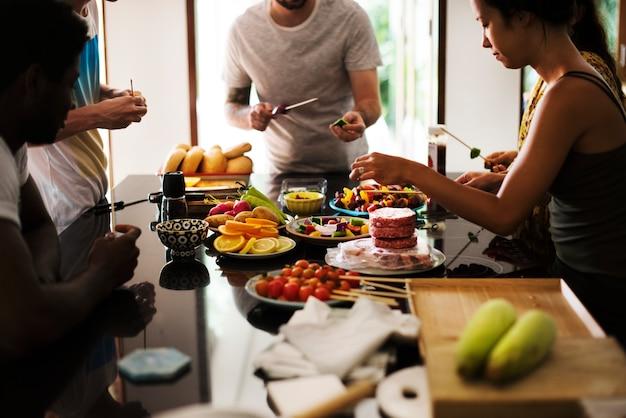 Eine abwechslungsreiche gruppe von freunden, die zusammen in der küche einen grill vorbereiten
