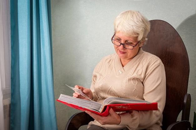 Eine ältere dame mit brille sitzt zu hause auf einem stuhl, schaut sich ein album mit fotos an und lächelt.