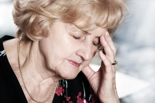 Eine ältere dame mit kopfschmerzen auf dunklem hintergrund