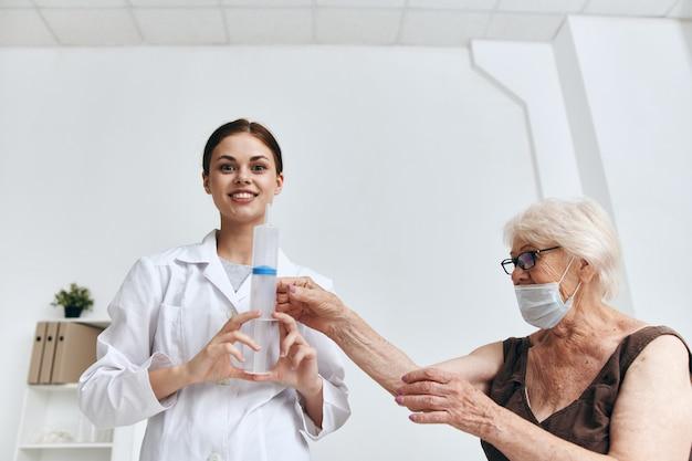 Eine ältere frau bei einem arzttermin eine spritze in den arm immunschutz