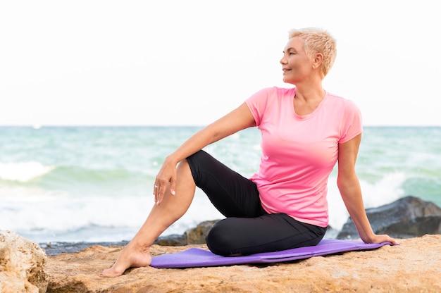 Eine ältere frau, die an einem strand vor yogaübung sitzt