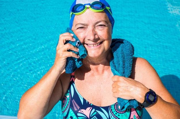 Eine ältere frau, die das schwimmbad genießt. ein volk mit großem lächeln. blaue badekappe und schutzbrille. gesunder lebensstil durch körperliche aktivität. sonniger tag und klares wasser