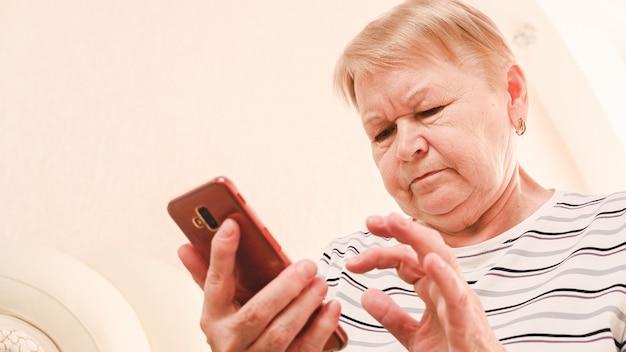 Eine ältere frau, die ein mobiltelefon untersucht.