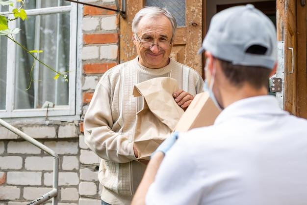 Eine ältere frau, die einen gehwagen benutzt, erhält mahlzeiten von einem mann, der mit einer wohlwollenden gruppe arbeitet, die lebensmittel an diejenigen liefert, die aufgrund des coronavirus covid19 einem hohen risiko ausgesetzt sind.