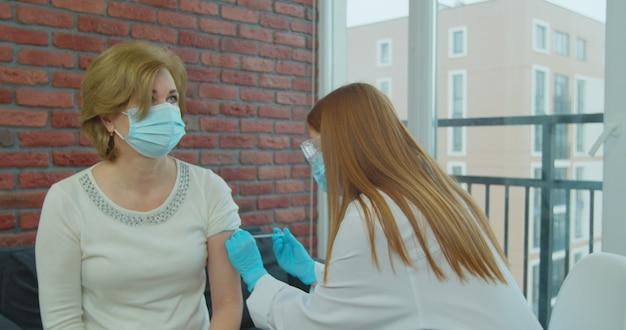 Eine ältere frau, die einen impfstoff gegen coronavirus erhält, ein arzt, der eine maske und handschuhe mit einer spritze trägt, injiziert einem reifen älteren patienten.