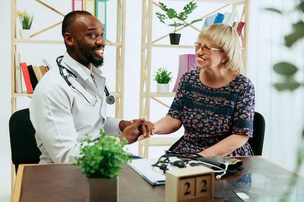 Eine ältere frau, die einen therapeuten in der klinik besucht, um sich beraten zu lassen und ihre gesundheit zu überprüfen.