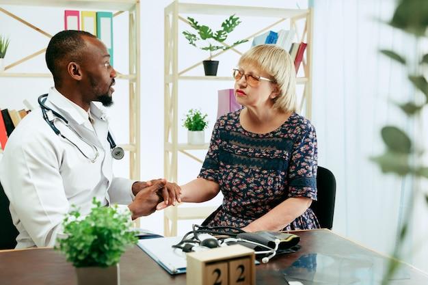 Eine ältere frau, die einen therapeuten in der klinik besucht, um sich beraten zu lassen und ihre gesundheit zu überprüfen