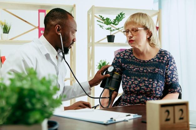 Eine ältere frau, die einen therapeuten in der klinik besucht