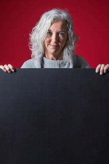 Eine ältere frau, die hinter dem unbelegten schwarzen plakat gegen roten hintergrund steht