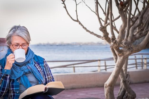 Eine ältere frau genießt ihr hobby, indem sie ein buch liest, das nahe dem strand sitzt und einen tee trinkt. horizont über dem wasser. ein einziger mensch mit brille und grauen haaren