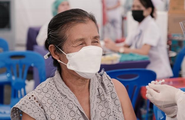 Eine ältere frau hat sich in einem feldkrankenhaus mit medizinischem personal gegen coronavirus covid19 geimpft