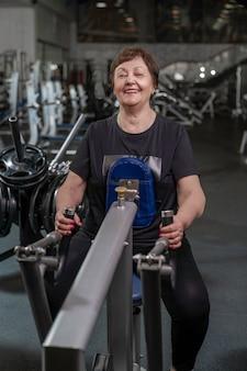 Eine ältere frau im fitnessstudio führt kreuzheben in einem horizontalen block durch