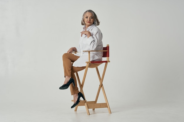 Eine ältere frau in einem weißen hemd sitzt auf einem stuhl und posiert