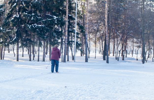 Eine ältere frau in einer jacke beim skifahren in einem winterpark, eine ansicht von hinten.